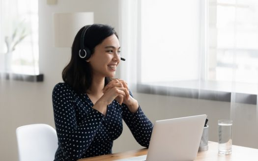 Woman in front of computer talking on headset
